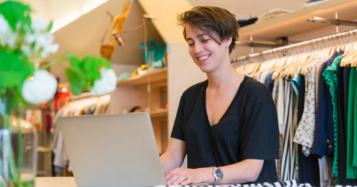 Woman smiling while using laptop - Growing Your Business With Grants Image