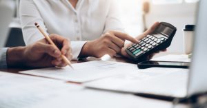 Woman calculating number on a calculator - How effective is your business structure blog image