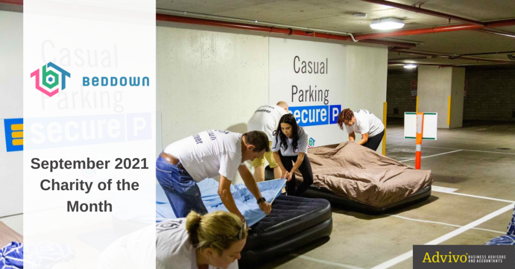 Beddown volunteers setting up beds in a parking lot - Charity of the Month image